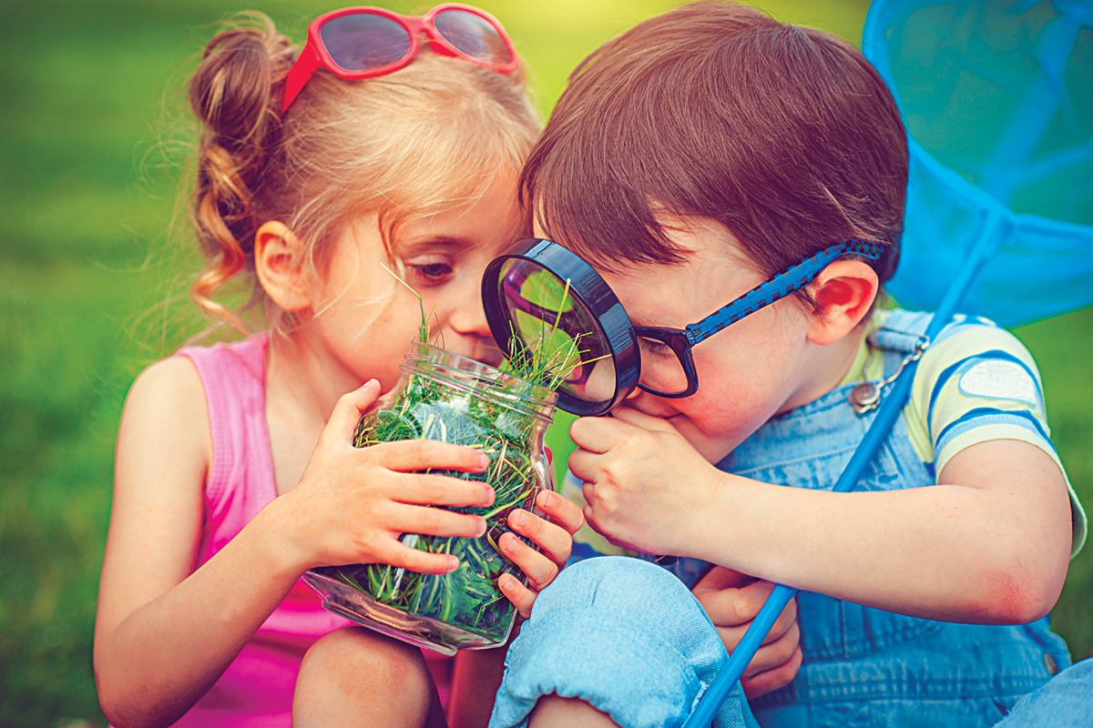 Two kids looking inside a jar with a magnifying glass
